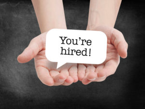 hands with you're hired sign indicates the start of a new-hire onboarding program